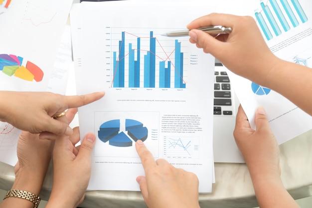 Mãos que apontam para um documento estatístico