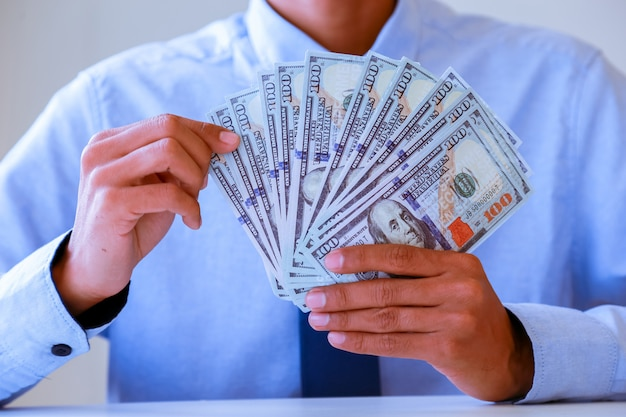 Mãos que contam o dinheiro - cédulas do dólar de estados unidos (usd).