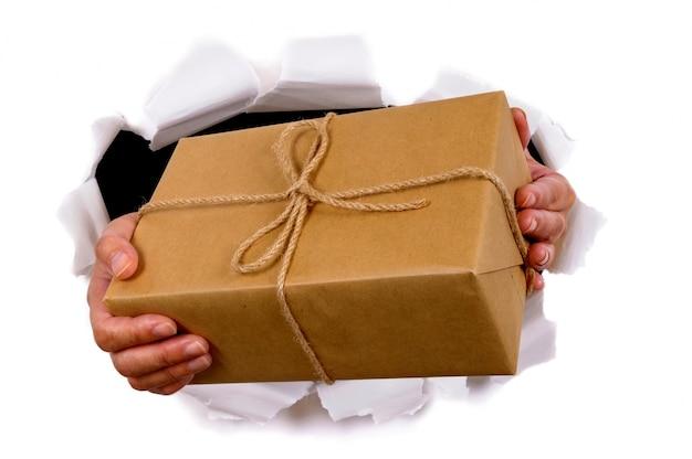 Mãos que entrega o pacote através do fundo de papel rasgado branco