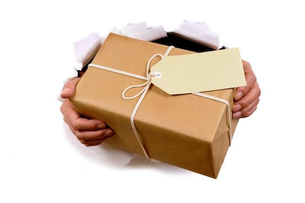 Mãos que entrega o pacote de correio através fundo de papel rasgado branco