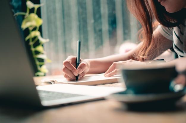 Mãos que escrevem perto acima. trabalhando com documento. mãos de mulher segurando a caneta e lista para fazer a lista.