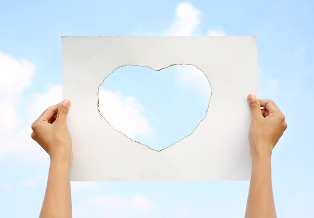 Mãos que guardam a folha de papel com queimadura na forma do coração contra o céu da nuvem.