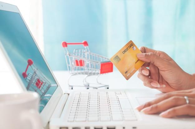 Mãos que guardam o cartão de crédito e que usam o laptop com fundo do carrinho de compras.