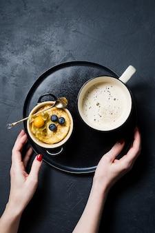 Mãos que guardam uma bandeja de pudim de arroz e de uma xícara de café.