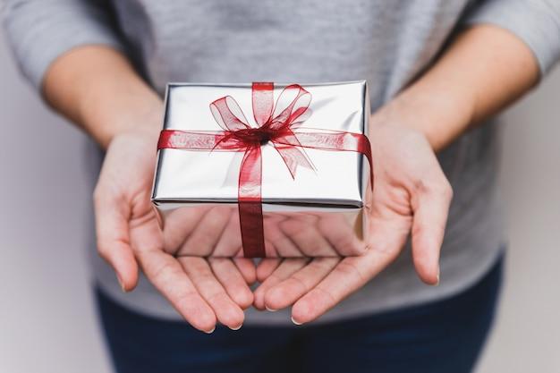 Mãos que prendem um presente de prata