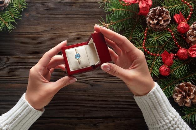 Mãos que prendem uma caixa com um anel com uma pedra azul