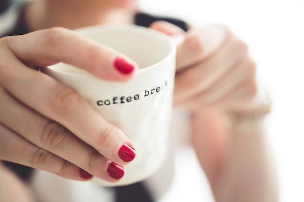 Mãos que prendem uma chávena de café