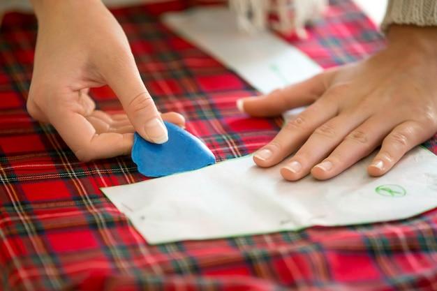 Mãos que trabalham com um padrão de costura