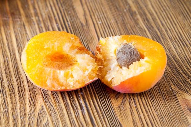 Mãos quebradas nas duas metades de damasco maduro de laranja