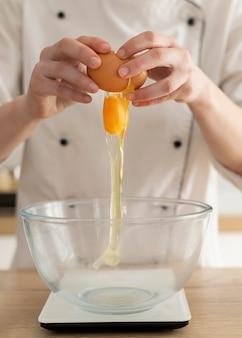 Mãos quebrando ovo de perto