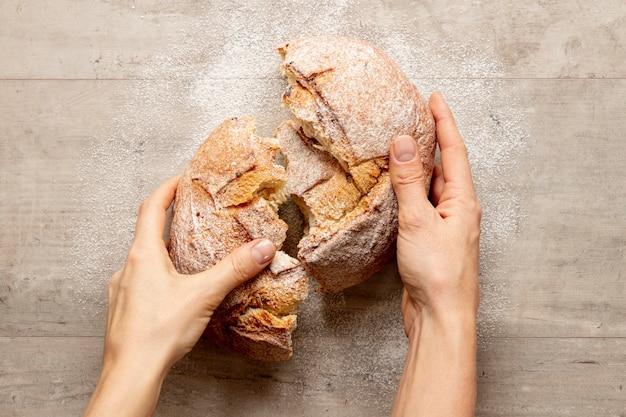 Mãos quebrando um pão delicioso