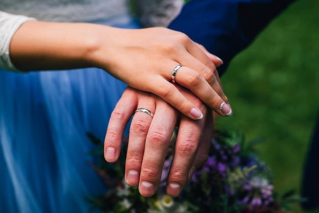 Mãos recém-casados noivos com anéis no casamento