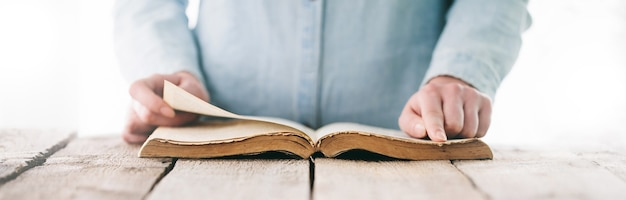 Mãos rezando com uma bíblia