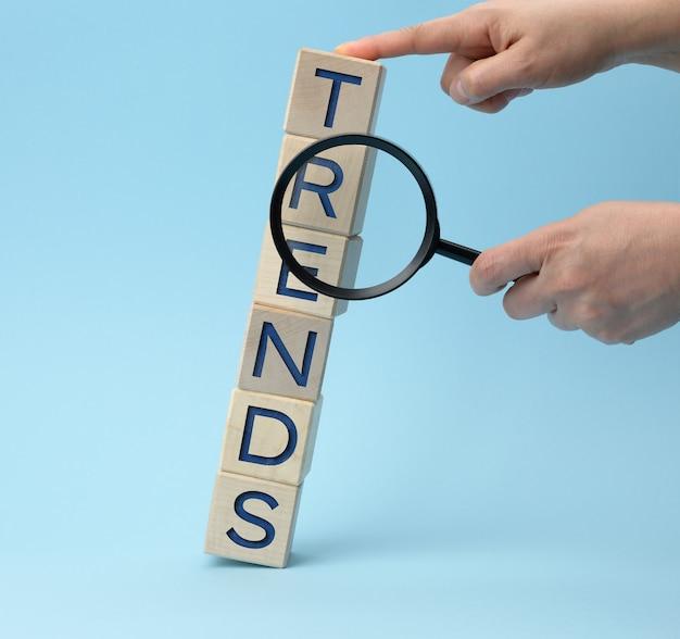 Mãos sacudindo uma lupa e cubos de madeira com as tendências de inscrições