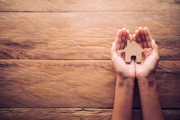 Mãos salvando pequena casa. seguro de casa