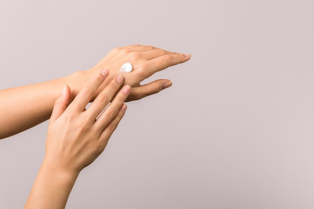 Mãos saudáveis de uma jovem mulher aplicar hidratante. skincare conceito beleza photoshoot