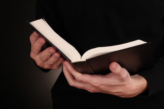 Mãos segurando a bíblia russa aberta sobre fundo preto
