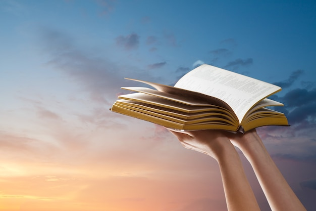 Mãos segurando a bíblia sobre o pôr do sol