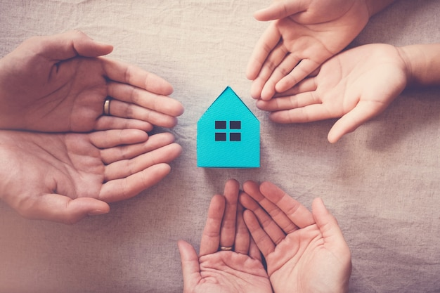 Mãos segurando a casa branca, a casa da família e o conceito de abrigo de desabrigados