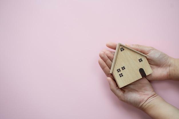 Mãos segurando a madeira da casa em fundo rosa pastel protegendo o conceito de seguro de casa