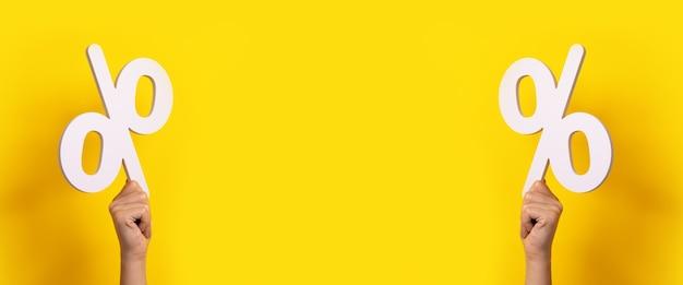 Mãos segurando a placa de porcentagem sobre fundo amarelo