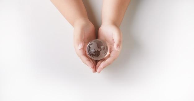 Mãos segurando a proteção de vidro do globo. conceito de meio ambiente