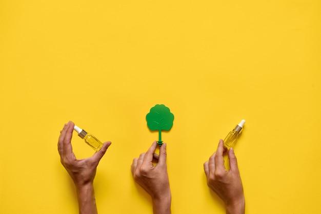 Mãos segurando árvores e óleos essenciais. medicina natural plana leigos. amarelo