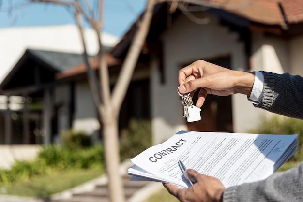 Mãos segurando as chaves da casa e contrato ao ar livre
