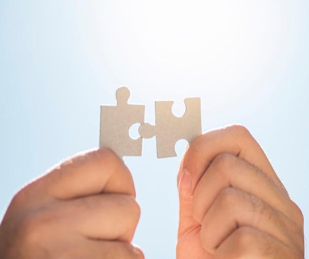 Mãos segurando as peças do puzzle