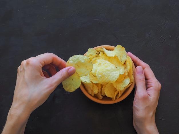 Mãos segurando batatas fritas numa superfície escura