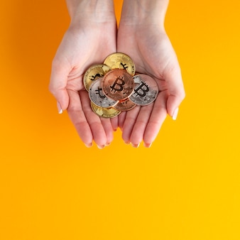 Mãos segurando bitcoin colorido diferente