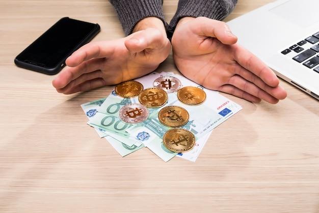 Mãos segurando bitcoin e notas de euro para troca em uma mesa.