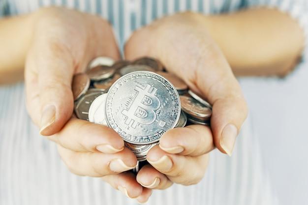 Mãos segurando bitcoins