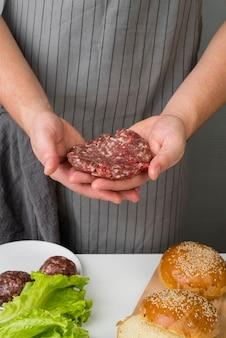 Mãos segurando carne para hambúrguer