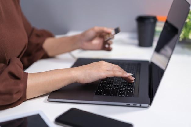 Mãos, segurando, cartão crédito, e, usando computador portátil, para, shopping online