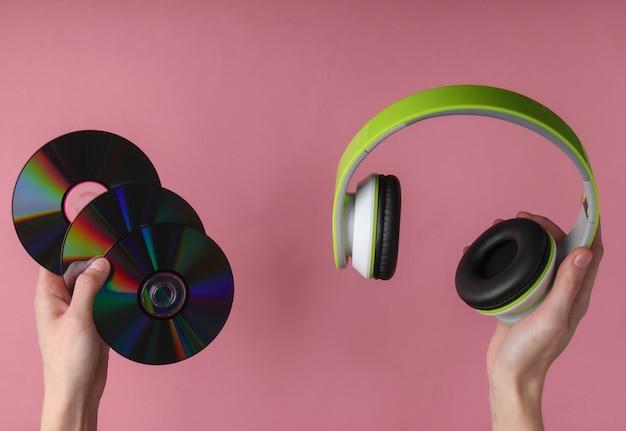 Mãos segurando cds e fones de ouvido na superfície rosa pastel