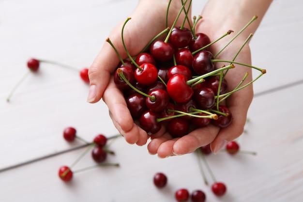 Mãos segurando cerejas frescas