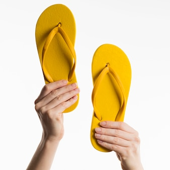 Mãos segurando chinelos