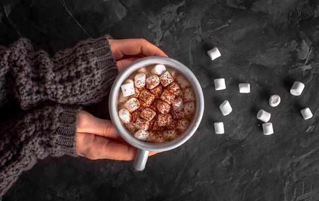 Mãos segurando chocolate quente com marshmallows e cacau em pó