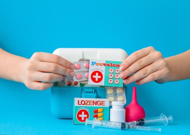 Mãos segurando comprimidos de um kit de primeiros socorros