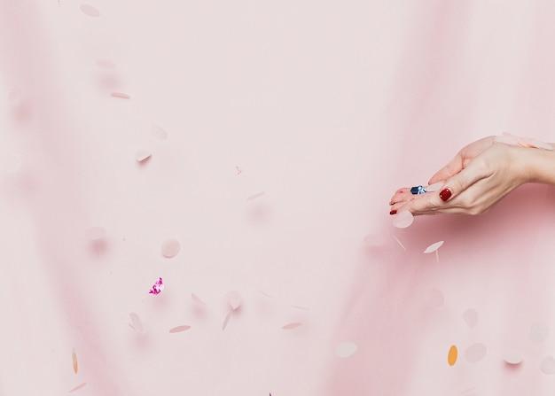 Mãos segurando confetes na frente de têxteis