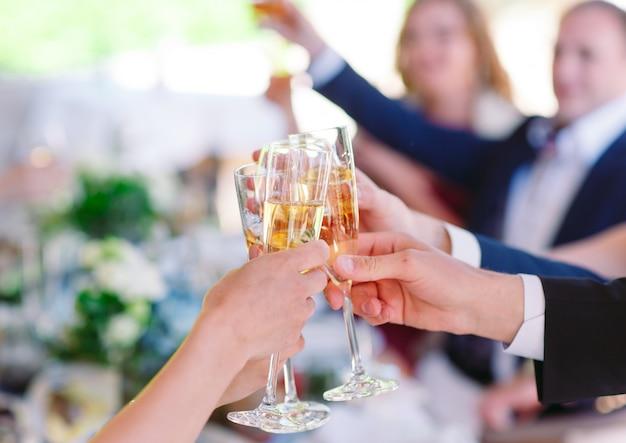 Mãos segurando copos e brindar, feliz momento festivo.
