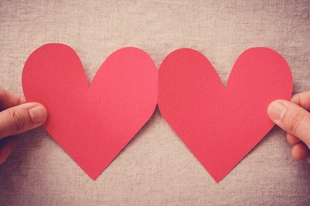 Mãos segurando coração vermelho, seguro de saúde, doação e conceito de amor