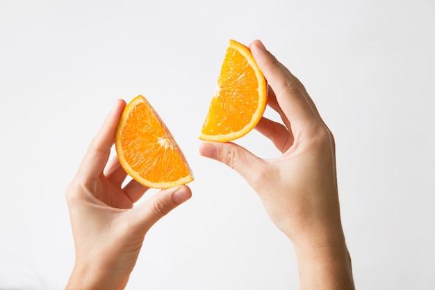 Mãos segurando cortadas seções laranja