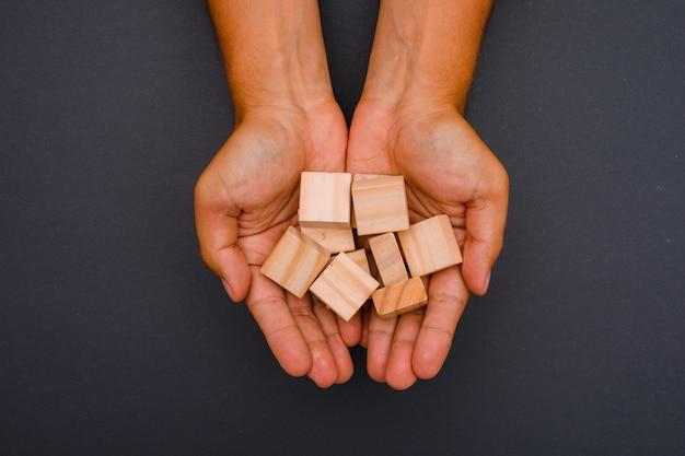 Mãos segurando cubos de madeira.