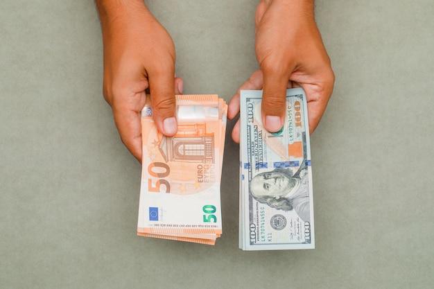 Mãos segurando dólares e euros.