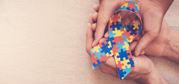 Mãos, segurando, enigma, fita, para, autismo, consciência, bandeira