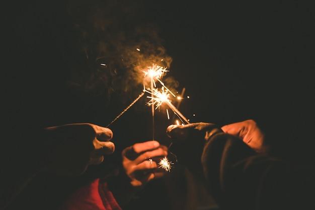 Mãos segurando estrelinhas para comemorar no período nocturno