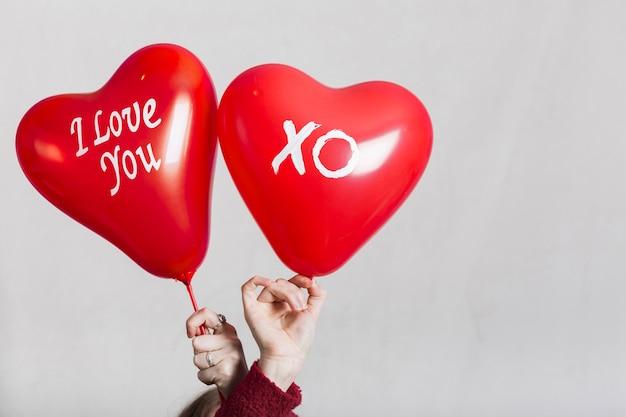 Mãos segurando eu te amo balões