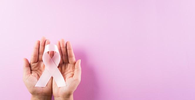 Mãos segurando fitas cor de rosa, conceito de conscientização do câncer de mama.